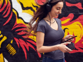Woman holding Chord Poly and listening with headphones
