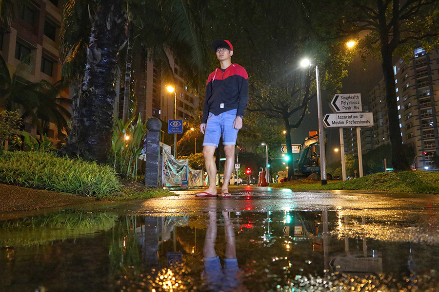 Man standing on street with puddle reflection