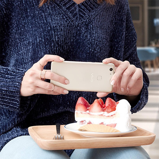 Woman taking photo of a cake using the Vivo V7+