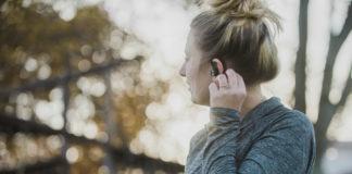 Woman using M4U TW1 earphones with phone