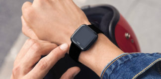 Pair of hands wearing Fitbit Versa