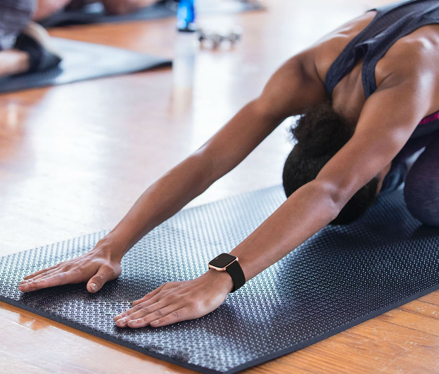 Person doing yoga while wearing Fitbit Versa