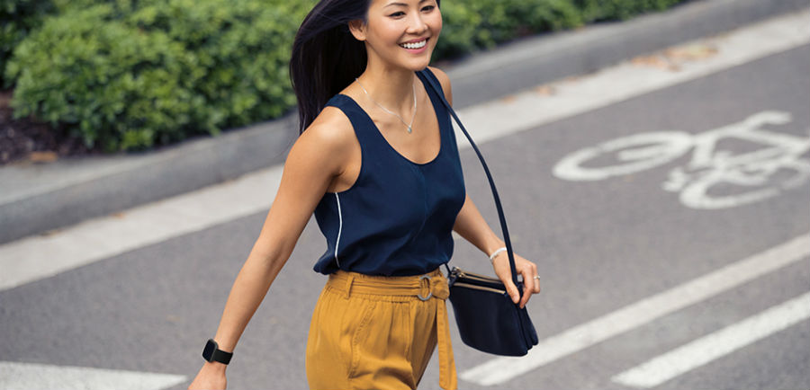 Woman crossing the road while wearing Fitbit Versa