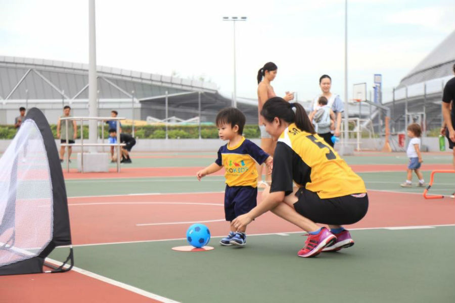 vivo Kids image of woman playing football with child
