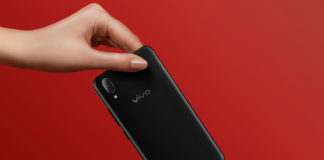 One hand passing Vivo X21 to another hand