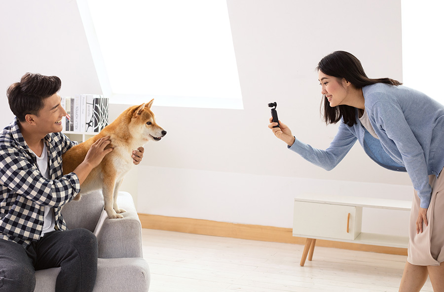 Woman taking a photo of a dog with a Mavic 2
