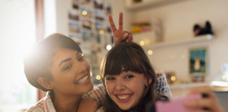 Playful young women taking selfie with camera phone