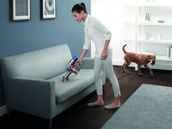 Woman Using Dyson V8 Cord-free vacuum cleaner on sofa
