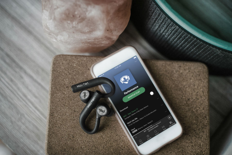 M4U TW1 earphones with paired phone playing Spotify