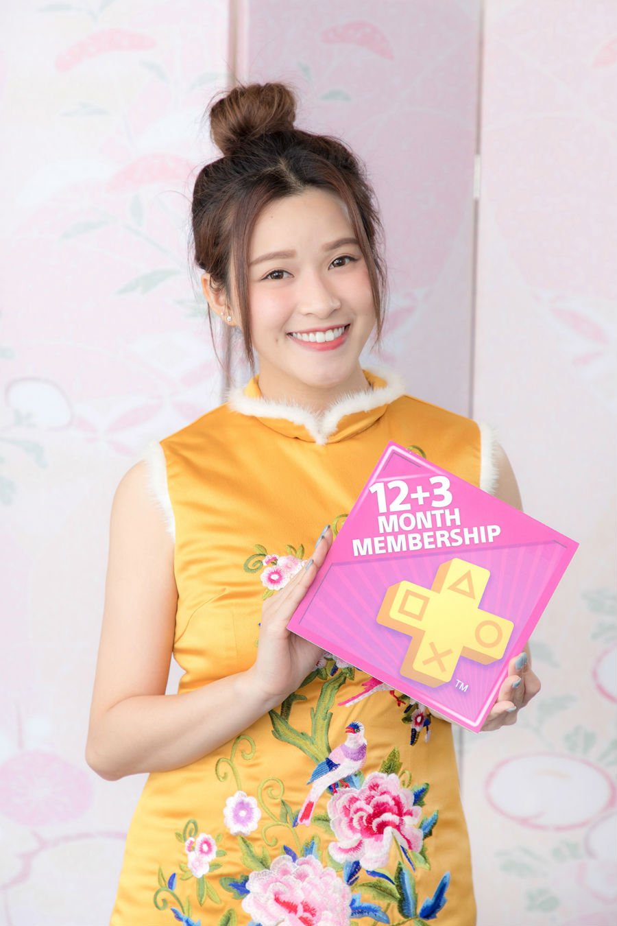 Girl holding sign for PS Plus 12 + 3 month promotion