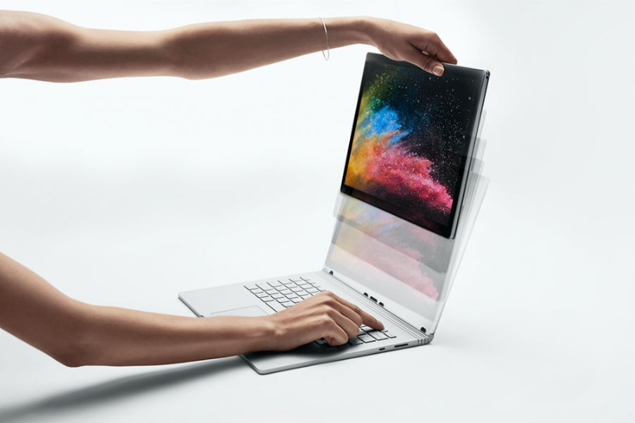 Woman transitioning Surface Book 2 from laptop to tablet