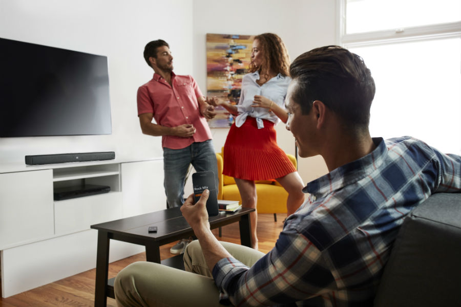 Party listening to music with JBL BAR Studio in living room