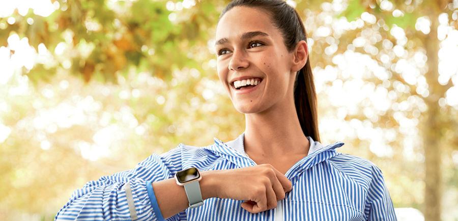 Woman wearing gray Fitbit Versa