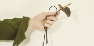 hand holding B&O Play Earset in Graphite Brown