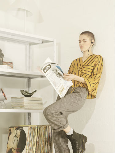 Woman wearing B&O Play Earset in Graphite Brown while reading newspaper