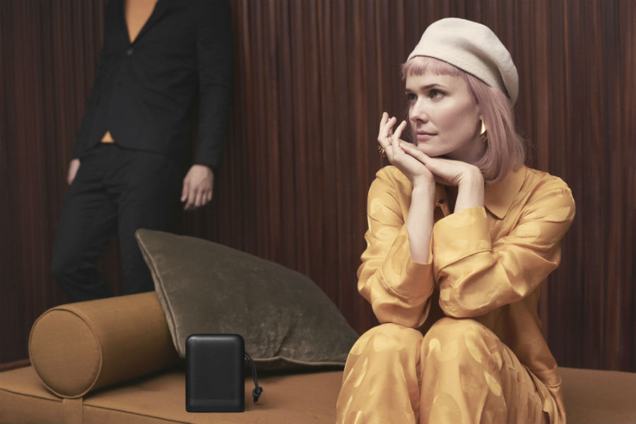 Woman in yellow sitting next to Beoplay P6