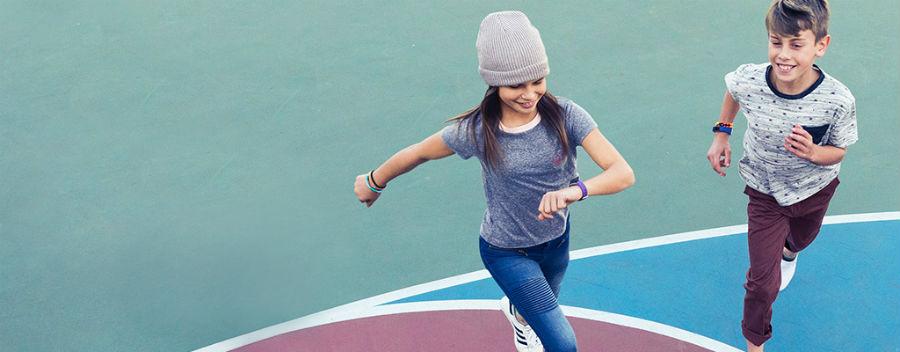Two children running around wearing Fitbit Ace