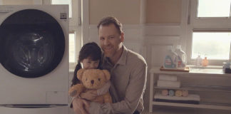 Father and daughter hugging in front of LG Steam Washer