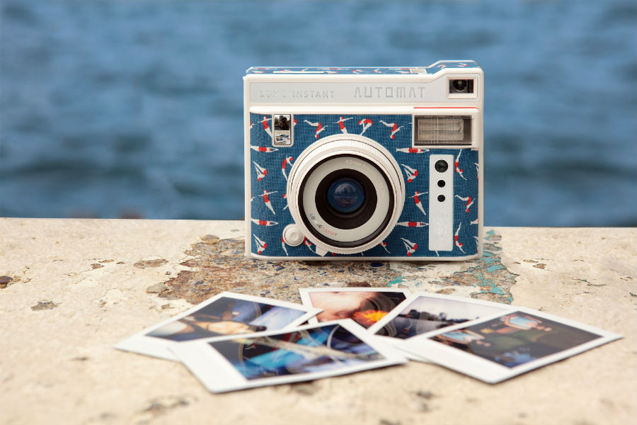Lomo'Instant Automat Riviera against sea backdrop with pictures in front