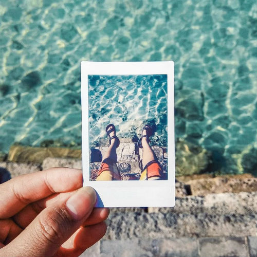 Hand holding instant polaroid of a pair of feet in water