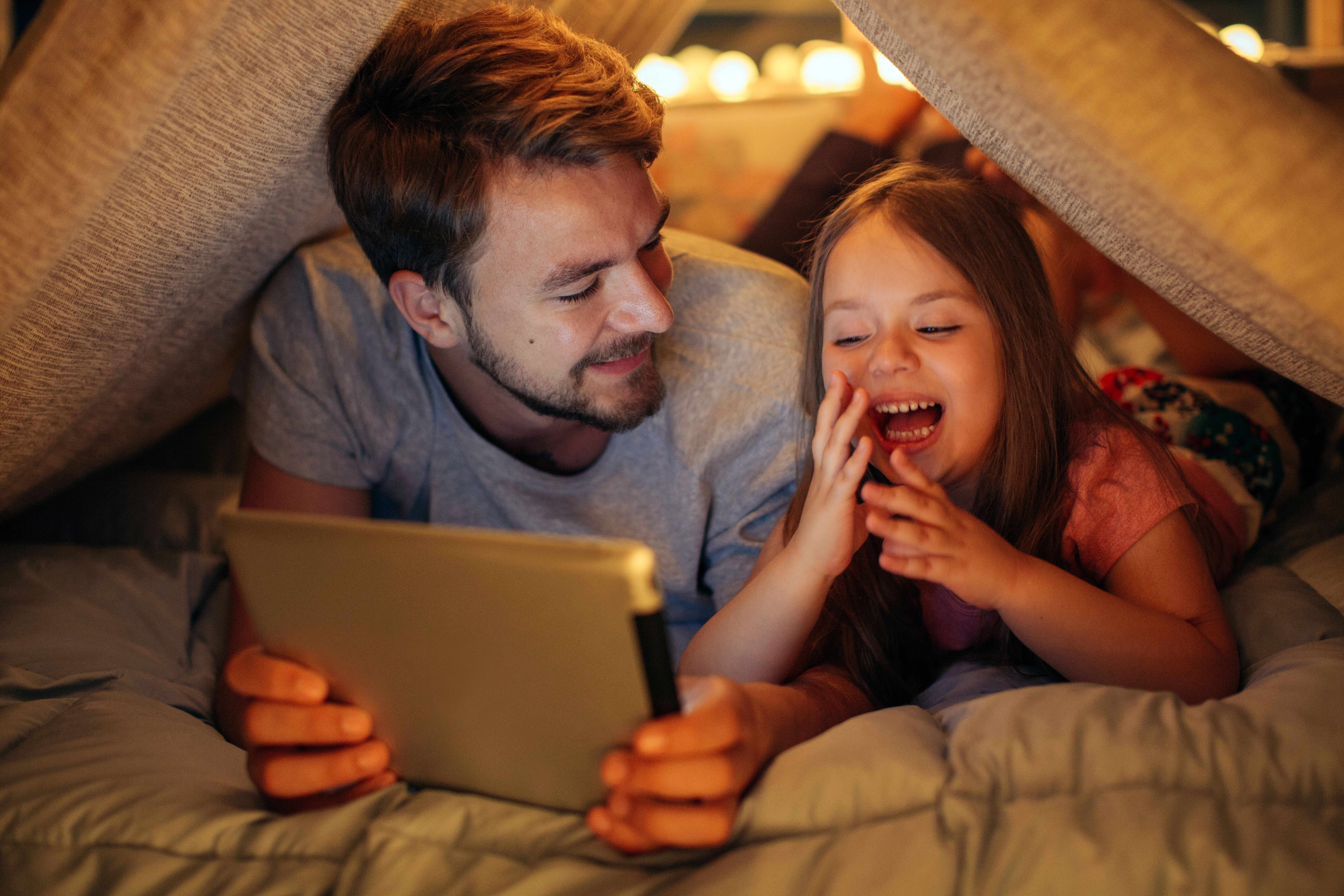 Father and daughter enjoying time over ipad at home
