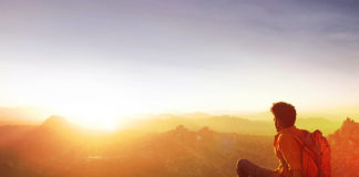 Man on top of mountain watching sunrise