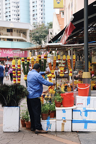 A man tending to his flower garland store