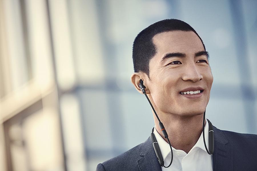 A man wearing Jabra Evolve 65e wireless neckband earbuds