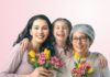 A granddaughter, mother and grandmother posing with flowers