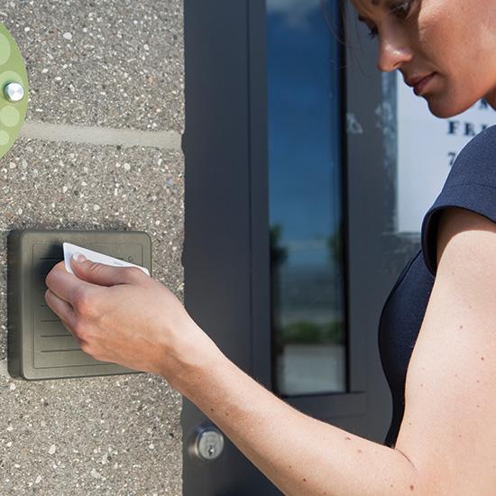 Woman holds a keycard up to a sensor