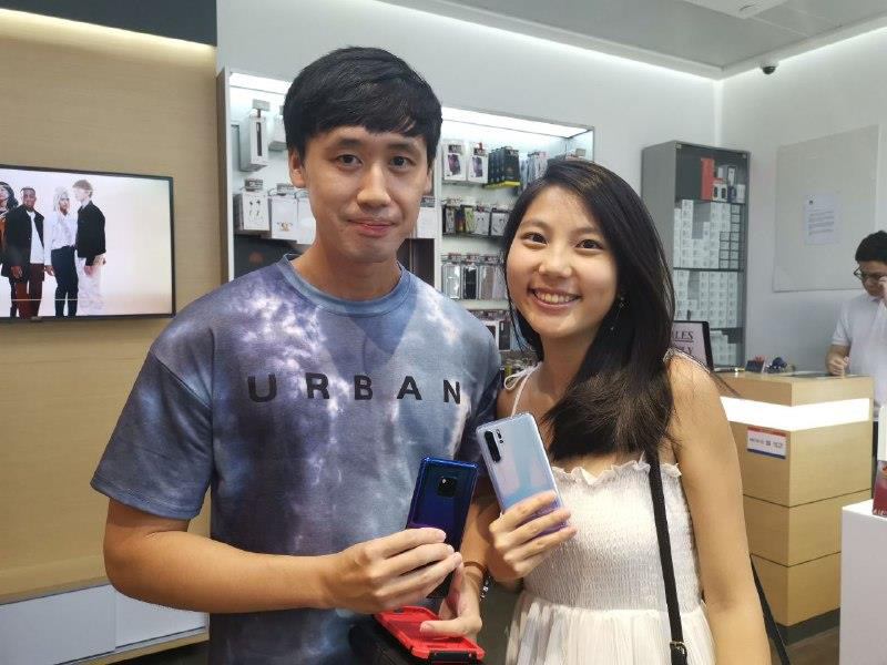Mr. James Lee (left) and his girlfriend, Ms. See Ying (right) posing for a photo with their Huawei phones