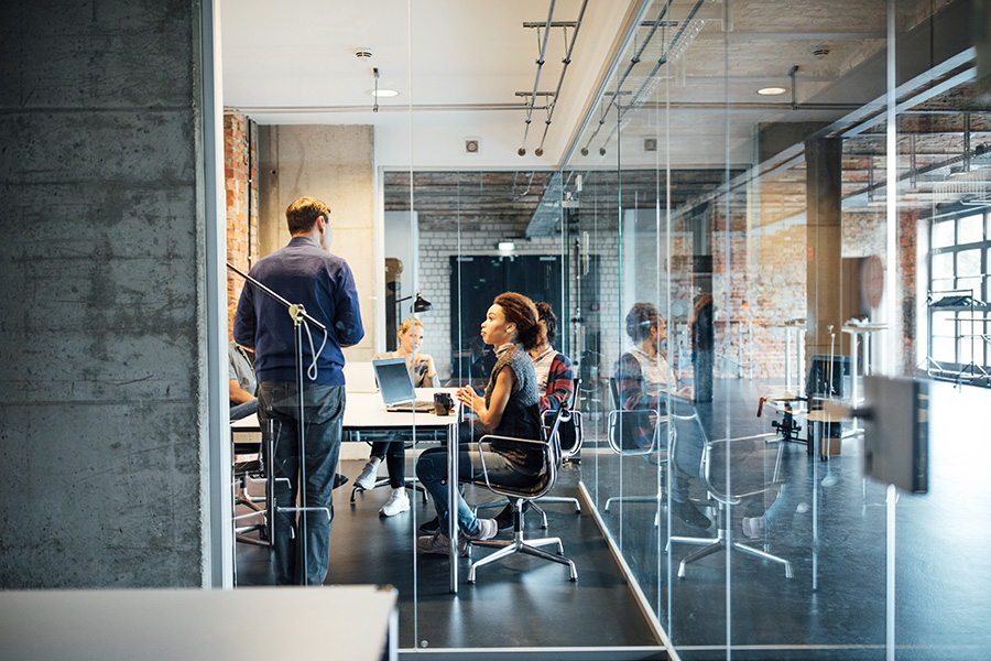 Businessman giving presentation to colleagues seen through glass doors at creative office