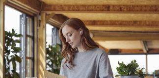 Lady wearing RHA TrueConnect true wireless earbuds in Cloud White outdoors