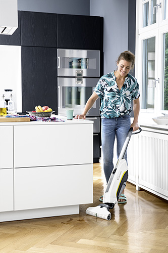 Woman using the Karcher FC 5 Cordless floor cleaner in the kitchen