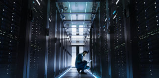 IT Technician Works on Laptop in Big Data Center full of Rack Servers. He Runs Diagnostics and Maintenance.