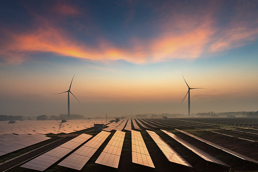 Wind and solar power plants in the dusk of the evening