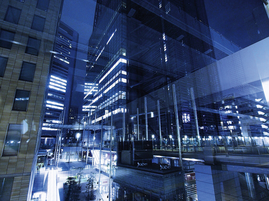 Modern Illuminated Office Building Reflections On Glass Window At Night