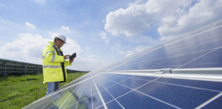 Man with digital tablet checking solar panels
