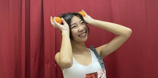 NXT Angel Averyl Loke posing with mandarin oranges and the CabinZero Hip Pack 2L