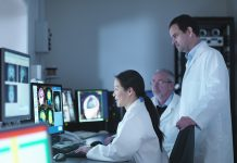 Doctors and scientists looking at screens of Magnetic Resonance Imaging (MRI) 3 Tesla twin speed scanner