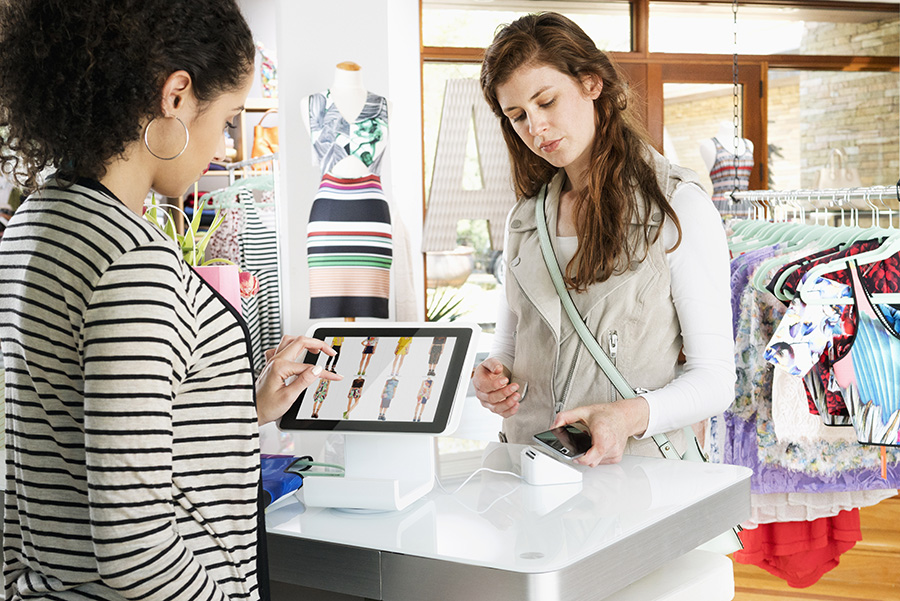 Woman shopping in clothing store paying with smart phone