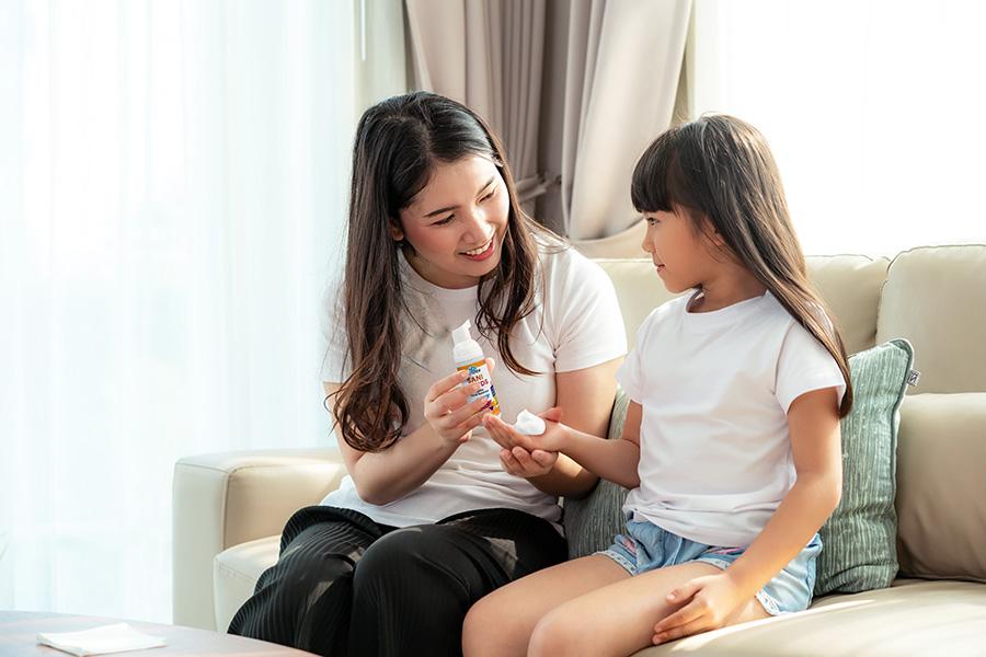 Mother using  Sureclean Sanihands on daughter