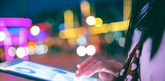 Hand using digital tablet at night
