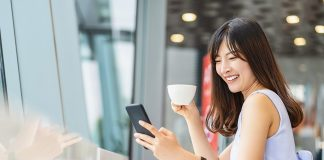 Asian woman using mobile phone and drinking a cup of coffee in modern coffee shop