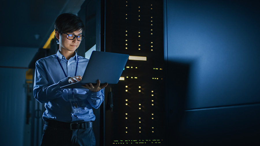 In Dark Data Center: Male IT Specialist Stands Beside the Row of Operational Server Racks, Uses Laptop for Maintenance. Concept for Cloud Computing, Artificial Intelligence, Supercomputer, Cybersecurity. Neon Lights